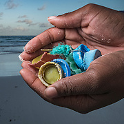 Hands holding plastic pollution like bottle caps and rope that washed up on a beach in The Bahamas.