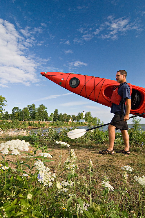 A kayaker carries his boat to launch on Lake Huron near the Point Aux Barques Lighthouse near Port Austin Michigan.