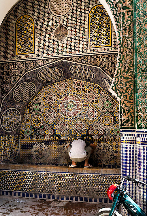Boy washing in public fountain in Fez medina, Morocco