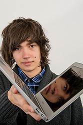 Teenage boy with laptop computer UK