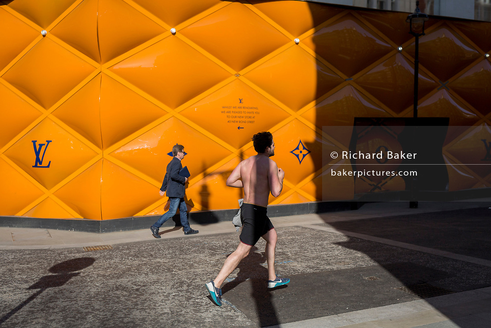 A shirtless runner passes the temporary renovation hoarding of luxury brand Louis Vuitton in New Bond Street, on 27th February 2019, in London, England.