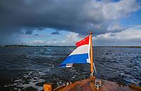 ALKMAAR - Alkmaardermeer, donkere lucht, met op de sloep de Nederlandse vlag, COPYRIGHT KOEN SUYK