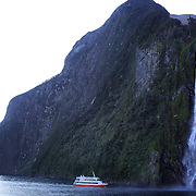 A tourist ship close to the spectacular Stirling Falls on Milford Sound..Milford Sound (Piopiotahi in Ma¯ori) is a fjord in the south west of New Zealand's South Island, within Fiordland National Park and the Te Wahipounamu World Heritage site. It has been judged the world's top travel destination and is acclaimed as New Zealand's most famous tourist destination..Milford Sound runs 15 kilometres inland from the Tasman Sea at Dale Point - the mouth of the fiord - and is surrounded by sheer rock faces that rise 1,200metres (3,900ft) or more on either side. Among the peaks are The Elephant at 1,517metres (4,977ft), said to resemble an elephant's head and The Lion, 1,302metres (4,272ft), in the shape of a crouching lion. Lush rain forests cling precariously to these cliffs, while seals, penguins, and dolphins frequent the waters and whales can be seen sometimes..Milford Sound sports two permanent waterfalls all year round, Lady Bowen Falls and Stirling Falls. After heavy rain many hundreds of temporary waterfalls can be seen running down the steep sided rock faces. .The beauty of this landscape draws thousands of visitors each day, with between 550,000 and 1 million visitors in total per year. This makes the sound one of New Zealand's most-visited tourist spots, and also the most famous New Zealand tourist destination.  Milford Sound, New Zealand. 29th April 2011. Photo Tim Clayton