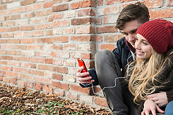 Young couple listening to music on mobile phone against brick wall, Munich, Bavaria, Germany