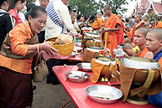 "Alms giving (tak bat) at the That Luang festival, Vientiane, Lao PDR. Pha That Luang is the national symbol and most important religious monument of Laos. Vientiane's most important Theravada Buddhist festival, ""Boun That Luang"", is held here for three days during the full moon of the twelfth lunar month (November). Monks and laypeople from all over Laos congregate to celebrate the occasion with three days of religious ceremony followed by a week of festivities, day and night. The procession of laypeople begins at Wat Si Muang in the city centre and proceeds to Pha That Luang to make offerings to the monks in order to accumulate merit for rebirth into a better life. The religious part concludes as laypeople, carrying incense and candles as offerings, circumambulate Pha That Luang three times in honor of Buddha."