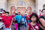05 OCTOBER 2013 - PHOENIX, ARIZONA:  Immigrants watch marchers pass a Catholic church in Phoenix during an immigration march. More than 1,000 people marched through downtown Phoenix Saturday to demonstrate for the DREAM Act and immigration reform. It was a part of the National Day of Dignity and Respect organized by the Action Network.    PHOTO BY JACK KURTZ