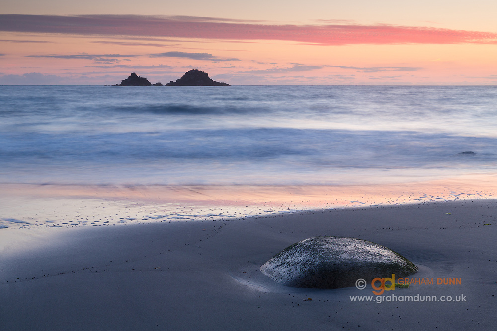Dusk colours reflect in receding low tide waters at Cornwall's stunning Porth Nanven beach. The Brisons islands can be seen on the horizon. Summer in The Cot Valley, England, UK. July, 2014.