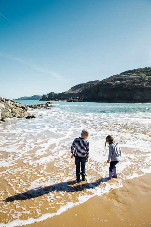 Children playing in the sea at Greve de L'Ecq beach in Spring, a popular beach with tourists and visitors to Jersey, CI