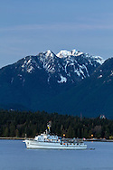 The fishing charter yacht M.V. Edgewater Fortune anchored in Vancouver's English Bay.  In the background is Stanley Park, Crown, Goat and Grouse Mountains with some fresh, spring snowfall. Photographed from Kitsilano Beach Park in Vancouver, British Columbia, Canada.