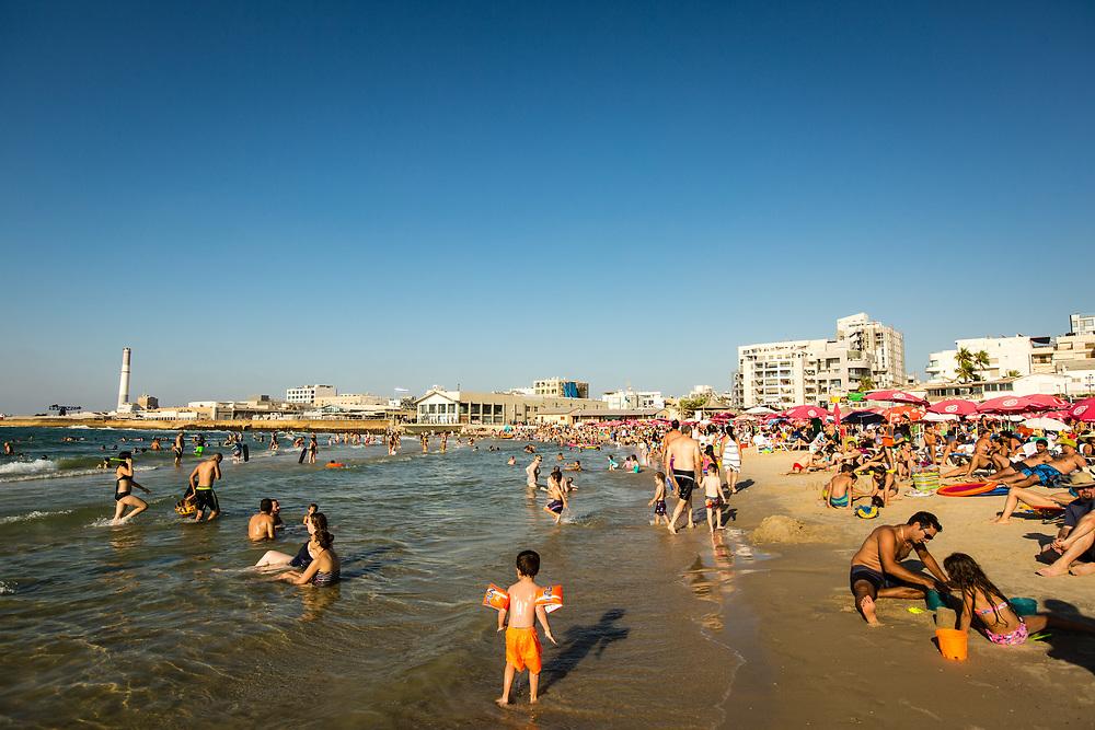 People are seen on Metzizim Beach in Tel Aviv's Merkaz Hair neighborhood