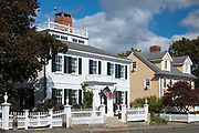 Elegant traditional wooden clapboard house with patriotic Stars and Stripes flag at Manchester-by-the-Sea. Massachusetts, USA