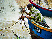 23 AUGUST 2018 - TELUK KUMBAR, PENANG, MALAYSIA: A man unties his fishing boat from a flood control gate in Teluk Kumbar on the island of Penang. Fishermen on Penang, an island off the west coast of mainland Malaysia, are being pressured by the island's resort development and reduce catches in the waters off Malaysia.     PHOTO BY JACK KURTZ