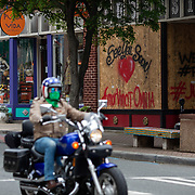 """CHARLOTTE NC - MAY 8:  A person wearing a face mask rides through an intersection in front of boarded up windows of a tattoo shop in the NoDa neighborhood in Charlotte, NC on May 8, 2020. Tattoo parlors still must remain closed but other commercial businesses that were deemed """"non-essential"""" are able to reopen at 5pm on May 8th under North Carolina Governor, Roy Cooper's phase 1 plan to reopen the state economy. (Logan Cyrus/ Bloomberg )"""