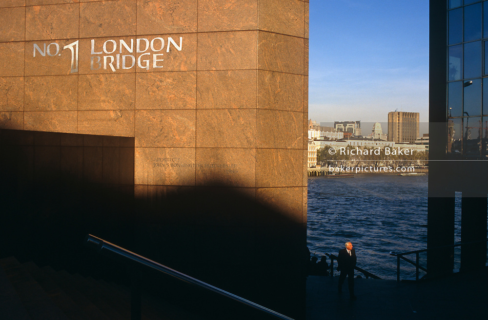A lone businessman walks along the River Thames beneath the prestigious address of number 1 London Bridge, an office block situated on the far southern side of London's ancient Bridge. Late afternoon light shines on the corner pillar that bears the name of the building and that of the architect John S Bonnington Partnership, the building's designers. The sun also illuminates the head and shoulders of the middle-aged man who wears a dark suit and walks with hands in pockets. The rest of his body remains in shadow as do the steps he is about to climb up to bridge and pavement (sidewalk) level. Behind him the waves of the River Thames ripple and a vista of the northern bank and the ancient City of London London's oldest and richest autonomous region) can be seen in the distance. The original Roman and medieval bridges would have been near this point.