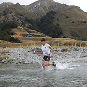 Runner Ann Scanlan crosses Moke Creek on the Ben Lomond High Country Station during the Pure South Shotover Moonlight Mountain Marathon and trail runs. Moke Lake, Queenstown, New Zealand. 4th February 2012. Photo Tim Clayton