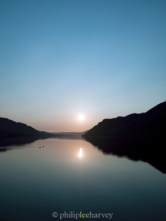 A dusky sunset over a lake at Ullswater, Lake District, UK