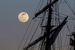 January 30, 2018 - St. Petersburg, Florida, U.S. - A jet flies in front of the rising moon January 30th 2018 along the St. Petersburg waterfront. Early January 31st will be the full moon and it will also be a blue moon (second full moon of the month) a super moon and a lunar eclipse. The eastern seaboard will only see a partial eclipse just before dawn but the west side of the US will see the total eclipse. (Credit Image: © Jim Damaske/Tampa Bay Times via ZUMA Wire)
