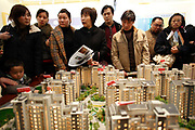 Potential buyers look at a model of a residential development at a  real estate fair in Shanghai, China on 15 March, 2009. For the past decade, Shanghai has underwent the largest reconstruction in recorded history, over 20 million square meters of land, approximately a third of Manhattan, were developed between year 200 and 2005 alone. Despite that however, housing prices have seen a rapid increase, putting the prospect of owning a decent sized home out of the reach of ordinary Chinese citizens, especially middle to low income families.