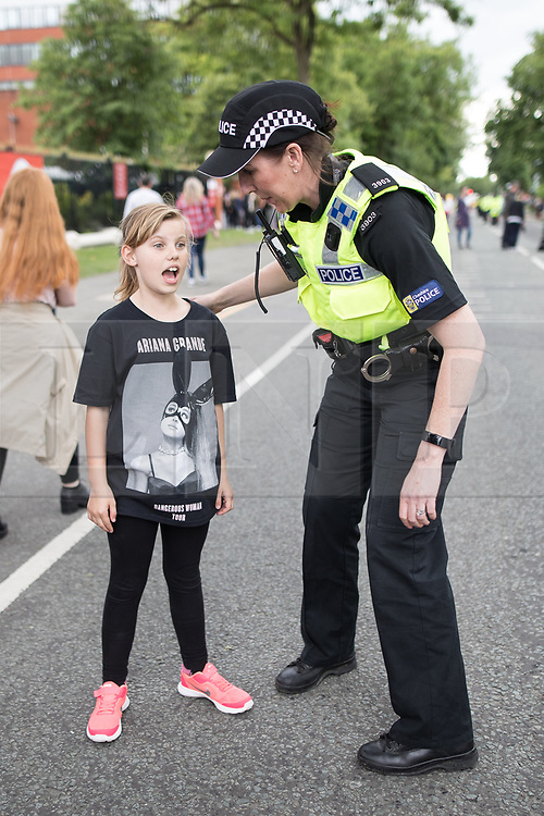 © Licensed to London News Pictures .  04/06/2017 . Manchester , UK . A police officer talks to a young Ariana Grande fan outside of the stadium . The One Love Manchester benefit concert for victims of the Manchester Arena terrorist attack , at the Emirates Old Trafford Cricket Stadium . Ariana Grande, Justin Bieber, Coldplay, Katy Perry, Miley Cyrus, Pharrell Williams, Usher, Take That, Robbie Williams, Black Eyed Peas and Niall Horan are amongst the performers. Photo credit : Joel Goodman/LNP