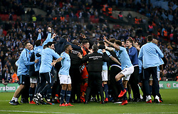 Manchester City players and staff celebrate on the pitch after winning the Carabao Cup Final at Wembley Stadium, London.