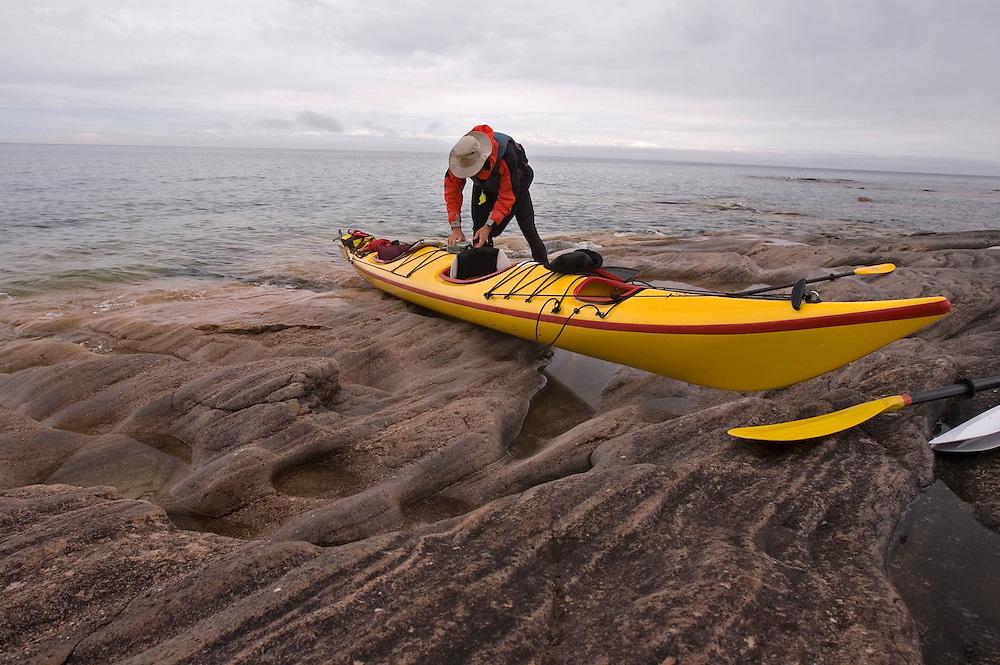A sea kayaker examines his tandem kayak after landing on an eroded sandstone beach at Lake Superior Provincial Park near Wawa Ontario Canada.