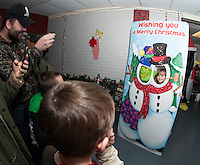 Leah Waniski gets her picture taken with the Grinch during the annual Christmas Village grand opening on Thursday evening.  (Karen Bobotas/for the Laconia Daily Sun)