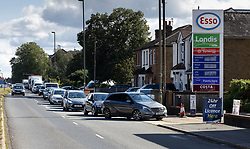 © Licensed to London News Pictures. 27/09/2021. London, UK. A long queue forms  outside an ESSO petrol station near Sunbury-on-Thames due to the current problems with the supply and distribution chain for fuel. Companies including BP and Shell have restricted deliveries due to the lack of HGV drivers. Photo credit: Peter Macdiarmid/LNP