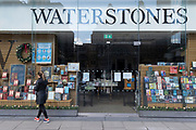 A woman looks in the window of The Victoria branch of closed bookseller chain, Waterstones during the third lockdown of the Coronavirus pandemic, on 5th February 2021, in London, England. Staff have launched a petition calling for Waterstones to top-up furloughed booksellers' pay to the minimum wage after recently filed accounts by the chain's owners, Elliott Advisors, showed 107 staff at the London hedge fund were paid a total of £93.3m.