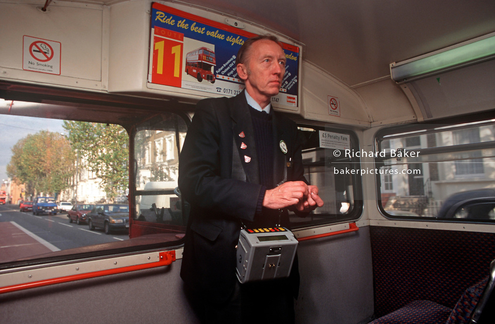 A 1990s bus conductor looks back along his bus during his shift on board of a red London Routemaster bus, on 18th February 1992, in London, England. (Photo by Richard Baker / In Pictures via Getty Images)