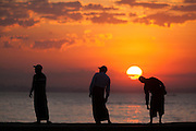 Three men doing morning exercise in silhouette as the sunrises