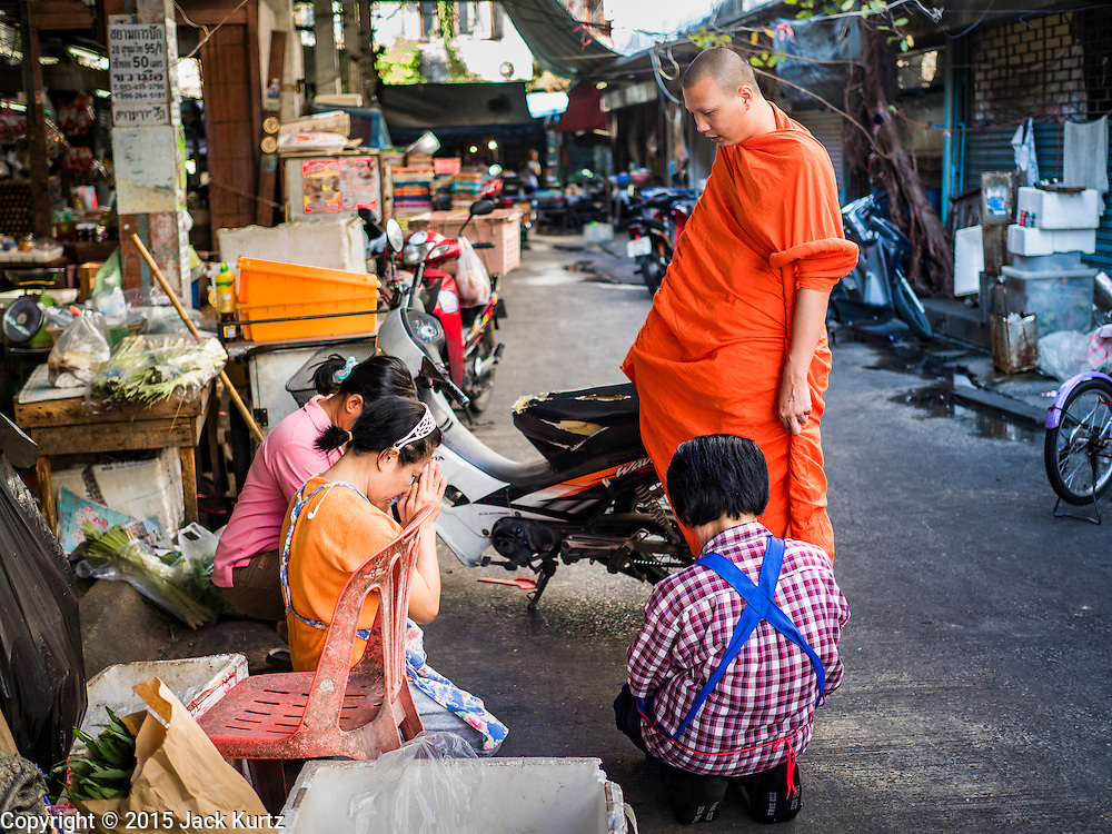 31 DECEMBER 2015 - BANGKOK, THAILAND: A Buddhist monk on his morning alms rounds in Bang Chak Market. The market is supposed to close permanently on Dec 31, 2015. The Bang Chak Market serves the community around Sois 91-97 on Sukhumvit Road in the Bangkok suburbs. About half of the market has been torn down. Bangkok city authorities put up notices in late November that the market would be closed by January 1, 2016 and redevelopment would start shortly after that. Market vendors said condominiums are being built on the land.          PHOTO BY JACK KURTZ