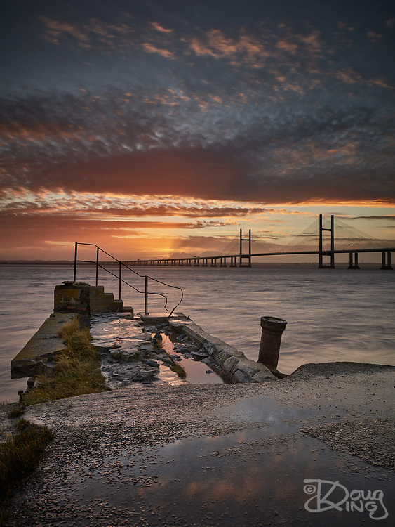The sun rises over the Prince of Wales Bridge, photographed across the abandoned jetty at Sudbrook.