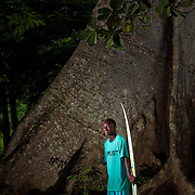 """Legend has it that The Cotton Tree in Robertsport, Liberia, is where the American Colonization Society tied up its ship in the late 19th century - the spot the Country was founded upon. Joseph Jenkins Roberts, the first president of Liberia (for whom Robertsport was named), is said to have carved his initials in the tree when he realized this would be the land where he would spend the rest of his life.<br /> <br /> The tree is also a marker for one of the nation's most famous waves that break directly in front of it: """"Cotton Trees"""" is a world-class pointbreak.<br /> I wanted to contrast this bastion of stability (the tree is estimated to be well over 500 years old) with the transient nature of the place these surfers thrive in - both their volatile country, and the ocean. While Liberia is hopefully seeking stability, the ocean is forever changing, never the same - but this famous tree is ancient and stable.<br /> <br /> The youths pictured here are litteraly the first generation of surfers in Liberia - they are the first citizens to ride waves on boards, and while many of them have fathers who are fisherman, these new wave riders are forming an entirely new relationship with the ocean due to their new sport. While I did want the images serious, I was very conscious of not wanting the image to be too dark. Yes, this country is coming out of a very dark time - the first elections after its civil war just happened days ago - but this is hopefully a new beginning, and these are the youth who will be shepherding it into being."""