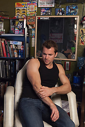 All American man in a tank top sitting in a tattoo parlor before getting a tattoo