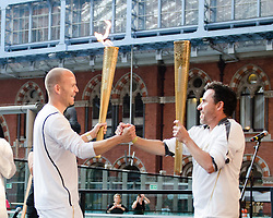 © Licensed to London News Pictures. 26/07/2012. London, UK.  London 2012 Olympics - the Olympic Torch at on its penultimate day (Day 69) of the Olympic Torch Relay at St Pancras International rail station .  Luke Corduner hands the torch over to Danny McCubbin.  Left - Luke, Right - Danny.  Photo credit : Richard Isaac/LNP