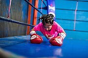 """18 DECEMBER 2104 - BANGKOK, THAILAND: A girl who wants to box does pushups in the ring at the Kanisorn gym. The Kanisorn boxing gym is a small gym along the Wong Wian Yai - Samut Sakhon train tracks. Young people from the nearby communities come to the gym to learn Thai boxing. Muay Thai (Muai Thai) is a Thai fighting sport that uses stand-up striking along with various clinching techniques. It is sometimes known as """"the art of eight limbs"""" because it is characterized by the combined use of fists, elbows, knees, shins, being associated with a good physical preparation that makes a full-contact fighter very efficient. Muay Thai became widespread internationally in the twentieth century, when practitioners defeated notable practitioners of other martial arts. A professional league is governed by the World Muay Thai Council. Muay Thai is frequently seen as a way out of poverty for young Thais and Muay Thai camps and schools are frequently crowded. Muay Thai professionals and champions are often celebrities in Thailand.     PHOTO BY JACK KURTZ"""