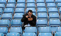 A fan in the stands eats a snack