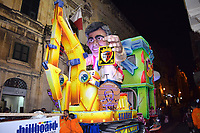 Man with JCB float illuminated at night