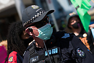 A police officer is seen during an Extinction Rebellion protest in Melbourne.  A small group of climate protesters marched from Flagstaff Gardens to The Queen Victoria Market and ending with two individuals gluing themselves together, and then glued themselves to Victoria Avenue outside of the Market. This comes as 5 new COVID-19 cases were uncovered in Melbourne's revamped Hotel Quarantine, breaking almost 40 days of virus free days. (Photo by Dave Hewison/Speed Media)