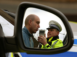PICTURE POSED BY MODEL<br /> Road Traffic constable John Parry from Police Scotland demonstrates breathalyser equipment at a drink-drive limit change awareness event at Lockerbie Police Station, Scotland, as the reduced drink-driving limit comes in to force at the end of this week.