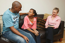 Professional interviewing teenage girl at home with father present.