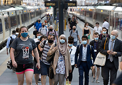 © Licensed to London News Pictures. 19/07/2021. London, UK. Passengers wear face coverings as they arrive at King's Cross Station on the morning of Freedom Day. All covid regulations in England are being scrapped from today even though infections and hospitalisations are on the increase. Photo credit: Peter Macdiarmid/LNP