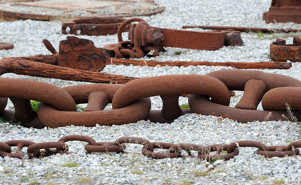 Rusty chains and other dock equipment displayed outside the Falkland Islands Museum in the old dockyard at Stanley.  Stanley, Falkland Islands.