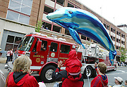 An inflatable dolphin floats over haed as spectators wave to truck No. 1 of the Charlottesville Fire Department during the Dogwood Parade held in Charlottesville, Va. photo/Andrew Shurtleff/