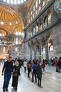 Muslim couple join tourists with smartphones at Hagia Sophia, Ayasofya Muzesi, mosque museum in Istanbul, Republic of Turkey