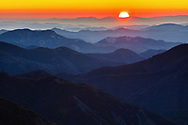 Sun rise in the red sky over an endless mountain range