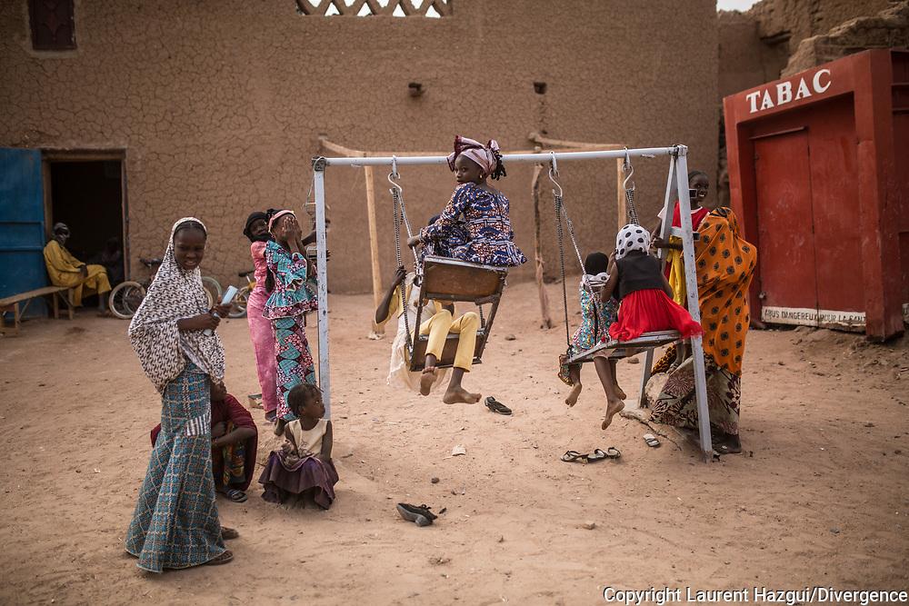 28012018. Niger. Agadez. Street photographie. Des petites filles s'amusent dans la rue et font de la balançoire.