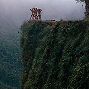 """Mountain Biking on Death Road, Bolivia...A tour group of young British and Australian tourists celebrate their success of completing the 64 kilometer journey mountain biking down the infamous narrow dirt road by posing nude for a photograph on a landmark bend of the road...The North Yugas Road is a 64 Kilometer road leading from La Paz to Corioico. It is legendary for it's extreme danger and in 1995 the Inter American Development Bank christened is as the """"world's most dangerous road"""".. The road was built in the 1930's during the Chaco War by Paraguayan prisoners to connect the Amazon rainforest region of Northern Bolivia to it's capital City La Paz. One estimate is that 200 to 300 travelers were killed yearly along the road. On 24 July 1983, a bus veered off the Yungas Road and into a canyon, killing more than 100 passengers in what is said to be Bolivia's worst road accident..A new stretch of the La Paz-Coroico highroad was opened in 2006 to bypass the notorious stretch known as death road..The danger of the road has now made it a popular tourist destination starting in the 1990's and drawing thrill-seekers and mountain bike enthusiasts who ride on the 64km mainly downhill stretch from La Cumbre, a 4,700 meter peak to Yolosa, a decent of 3600 meter's (11,800 feet). The journey includes breathtaking views of snow covered peaks and towering cliffs and starts along modern asphalted road before entering the jungle itself and the most dangerous and notorious part of the ride. The infamous narrow dirt road, most of the road no wider than 3.2meter's, is cut into the side of the mountain with sheer drops to the left of up to 600 meter's with virtually no safety rails on the winding steep decent..There are now many tour operators catering to this activity, providing information, guides, transport and equipment. Nevertheless, the Yungas Road remains dangerous. At least 13 of these cyclists died on the ride since 1998, the latest A 28-year-old Israeli traveler was killed in"""