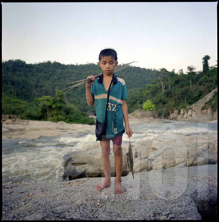 A vietnamese boy stands on a rock close to a river. He's holding fishing gear. Nghe An province, Vietnam, Asia