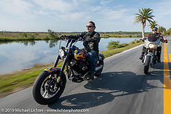 Bob Zeolla (L) riding his custom Harley-Davidson with his wife Andrea Labarbara on her Roland Sands RSD custom on a ride through Tomoka State Park during Daytona Beach Bike Week, FL. USA. Friday, March 15, 2019. Photography ©2019 Michael Lichter.